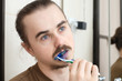 Man cleaning his teeth with blue color