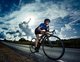 Fototapety Female cyclist cycling am The path in the woods and mountains