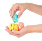 hand holding colorful macarons on white background - 105152823