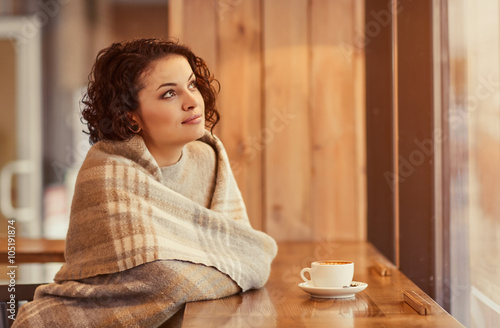 Pleasant woman sitting at the table Poster