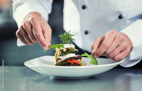 Chef in Restaurant garnishing vegetable dish