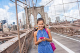 Fototapety Happy Asian woman using phone texting walking on Brooklyn bridge, New York city for social media or blogging. Tourist doing summer travel in Manhattan, USA.