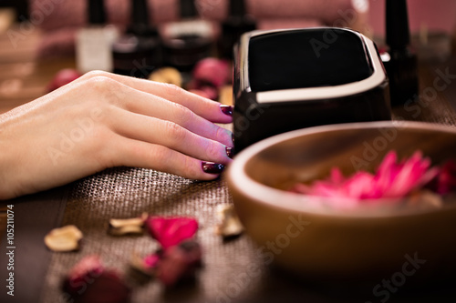 Closeup finger nail care by manicure specialist in beauty salon. Tableau sur Toile