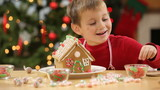Young boy builds gingerbread house