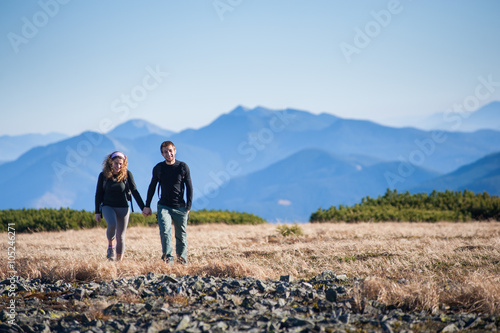 Poster Young happy couple hiking in the beautiful mountains on warm sunny fall day