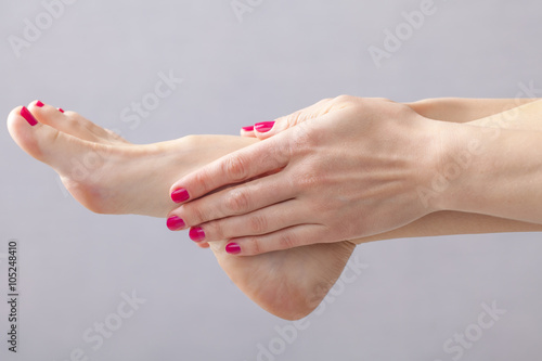 Deurstickers Pedicure female legs and hands manicure massage pedicure red nail nails