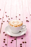Fototapety cup of cappuccino with heart foam, coffee beans on pink wooden background, drink hot product photography