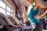 Two fit women running on treadmills in modern gym