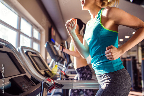 Wall mural Two fit women running on treadmills in modern gym