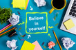 Believe in yourself. Office table desk with supplies, white blank note pad, cup, pen, pc, crumpled paper, flower on wooden background. Top view