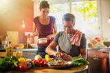 Fototapety Trendy couple cooking vegetables from the market in the kitchen