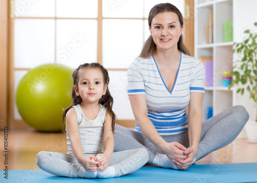 Fototapeta Happy mom and kid daughter spends time in the gym