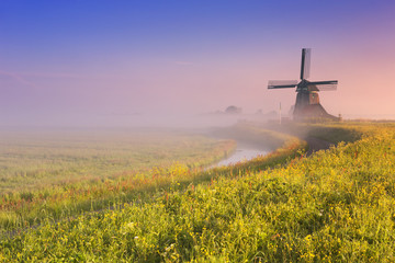 Traditional Dutch windmill at sunrise on a foggy morning