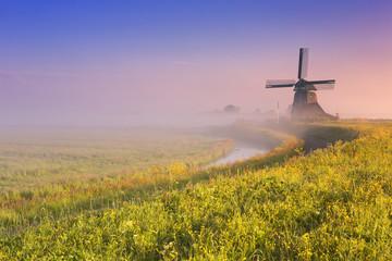 Traditional Dutch windmill at sunrise on a foggy morning