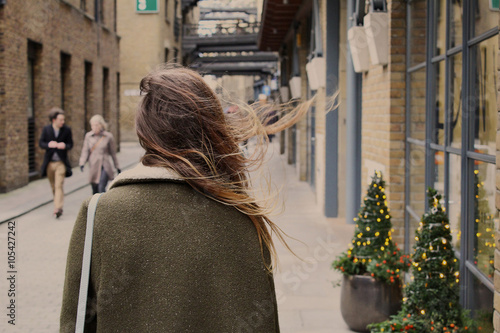 Young girl with dispelled hair walking down the street in the wind