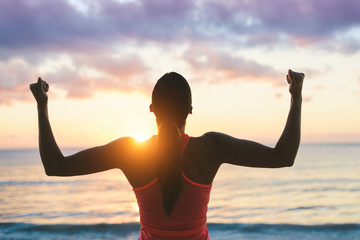 Fitness woman celebrating fitness workout success and motivation towards the sea and sunset.