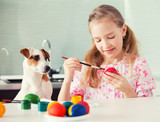 Girl with dog painting eggs