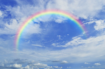 Rainbow with white clouds over blue sky