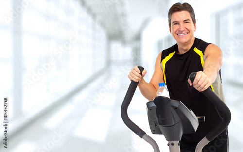 Man exercising on elliptical trainer. © Kurhan