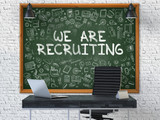 We are Recruiting - Handwritten Inscription by Chalk on Green Chalkboard with Doodle Icons Around. Business Concept in the Interior of a Modern Office on the White Brick Wall Background. 3D.