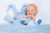Fototapety Baby boy playing with blue knitted bunny toy