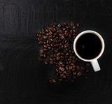Fototapety Dark coffee with roasted beans on natural slate stone background