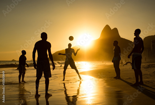 Silhouette of locals playing ball at sunset in Ipanema Beach, Rio de Janeiro, Brazil.