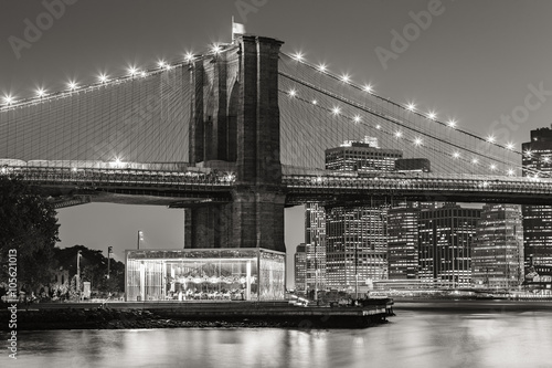 Black and White of  Brooklyn Bridge Tower at twilight with carousel and skyscrapers of Lower Manhattan. Financial District. New York City - 105621013