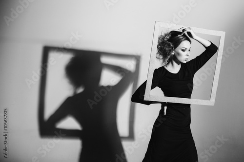 Сharismatic woman frame in his hands, fashion pose, black and white photo, stud