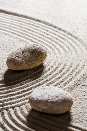 zen sand still-life - textured stones set on sinuous waves for concept of change or suppleness with inner peace, closeup