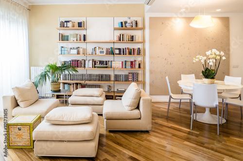 soggiorno in appartamento con tavolo rotondo, libreria a muro e parquet, curato e pulito in stile classico