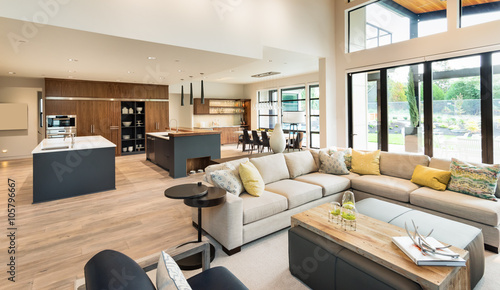 Beautiful living room interior in new luxury home with view of kitchen. Home interior with hardwood floors and open floorplan showing dining room, kitchen, and living room. Has high vaulted ceilings.