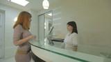 Patient and nurse conversing at hospital reception desk