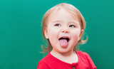 Fototapety Happy toddler girl sticking her tongue out in front of a chalkboard