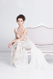 Beautiful young bride in a luxurious lace wedding dress. She sits on a white vintage sofa. She is an elegant and slim. The dress has a translusent silk train. Her hands are folded in elegant gesture.