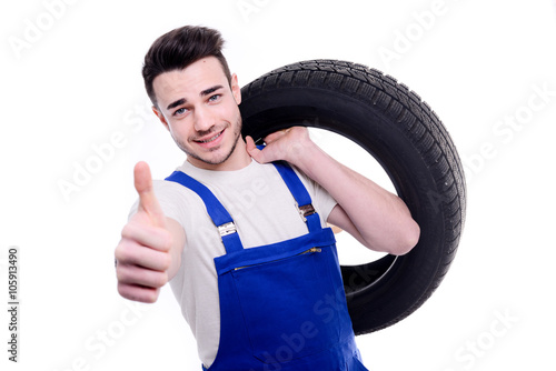 handsome young mechanic holding a tire isolated on white background