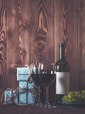 Bottle of wine, wineglasses, grape and gift boxes on wooden table. Retro style. Dark toned
