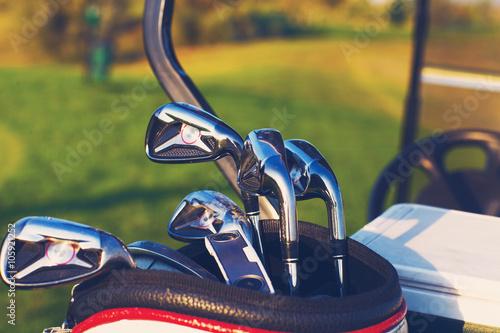 Fototapeta Golf clubs drivers over green field background