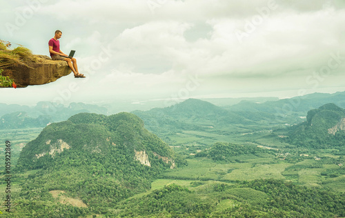 Man working with laptop sitting on the rocky mountain on beautiful scenic clif background. Thailand. Krabi .