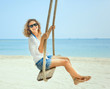Beautiful happy girl on a swing on the beach. Holiday, vacation,