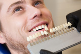 Close up portrait of Young man in dentist chair, Check and select the color of the teeth. Dentist makes the process of treatment in dental clinic office