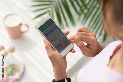 Girl using application on her smartphone to check health
