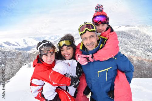 Parents giving piggyback ride to kids on ski slope