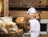 Mature bakery employee offering bread and different pastry for sale