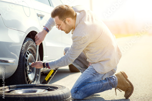 Changing tire on broken car on road