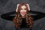 Fototapety Cheerful pretty young woman touching her long curly beautiful hair