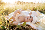 Funny twins sisters newborn babies lying on grass in summer day