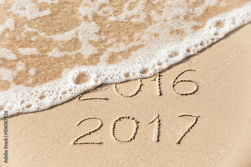 2016 2017 inscription written on wet yellow beach sand being washed by sea wave