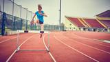 ragazza atletica salta ostacolo v pista
