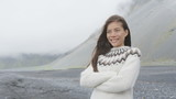 Happy young woman standing arms crossed against mountain in Icelandic sweater on Iceland. Beautiful female is wearing sweater. Attractive woman is looking away while enjoying vacation during winter.